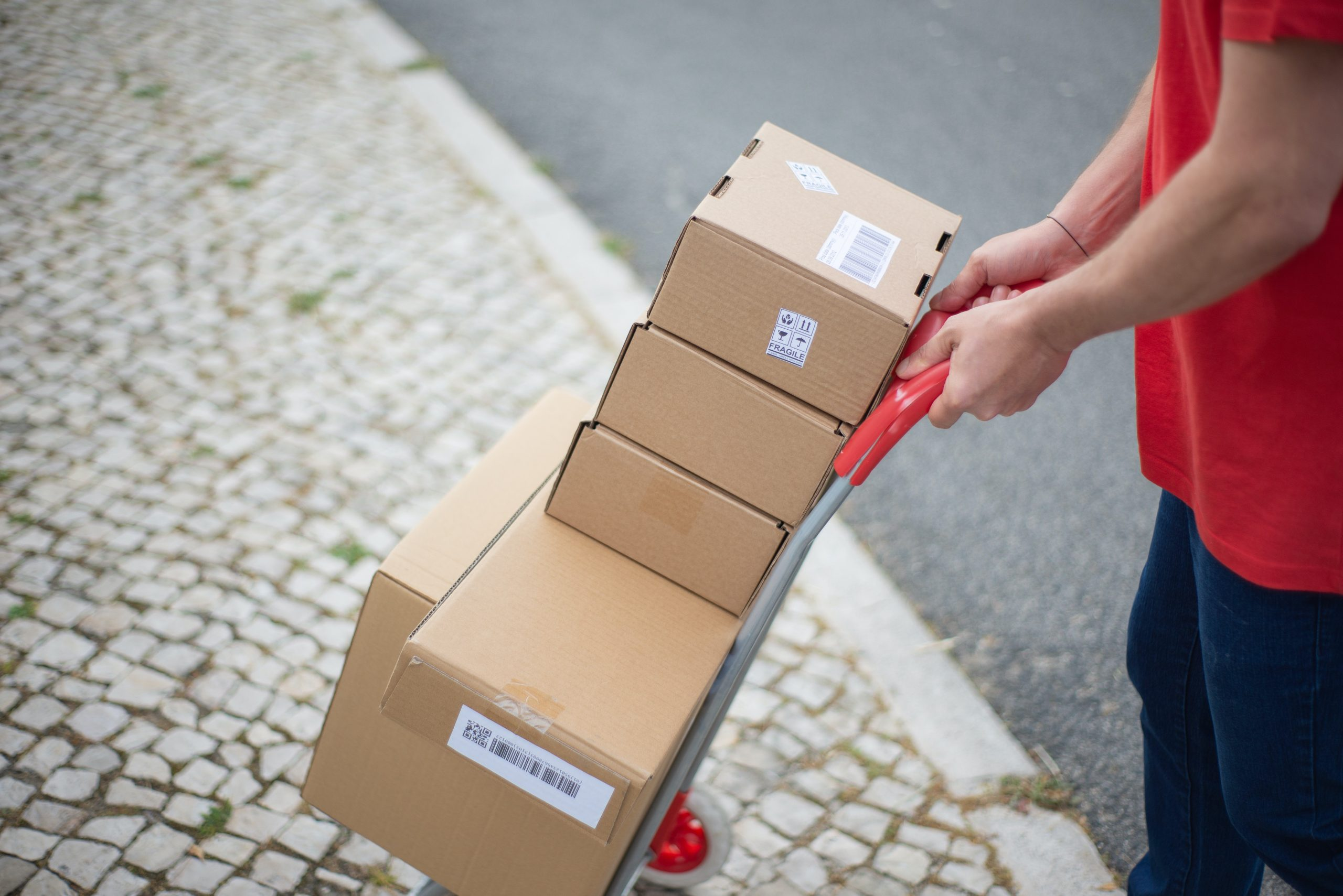 A delivery guy pushing a dolly with parcels